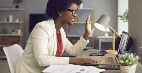 Vrouw thuis aan het werk en zwaait achter laptop naar videocall